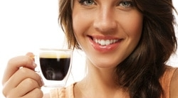 woman smiling with a tiny cup of coffee